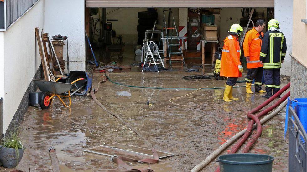 Hofeinfahrt und Garage voller Schlamm, die Feuerwehrleute halfen beim Reinigen.