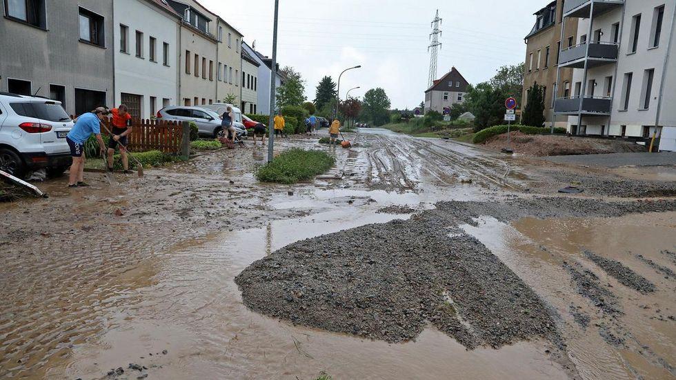 Anwohner am Dittrichbach rücken dem Schlamm zuleibe.